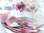 Festive wedding table setting with pink flowers napkins vintage cutlery glasses and candles bright summer table decor.