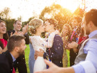 Full length portrait of newlywed couple and their friends at the wedding party showered with confetti in green sunny park