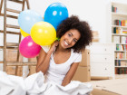 Happy African American Woman celebrating her move to a new house kneeling on the floor in the living room surrounded by crumpled paper holding colourful party balloons